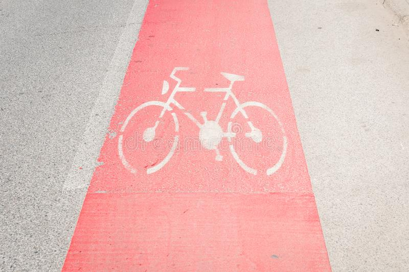 Bike lane painted in red as caution on the asphalt road with bicycle sign or symbol royalty free stock image