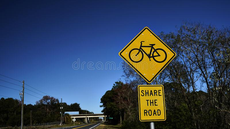 Bike lane road sign with street in background stock photo