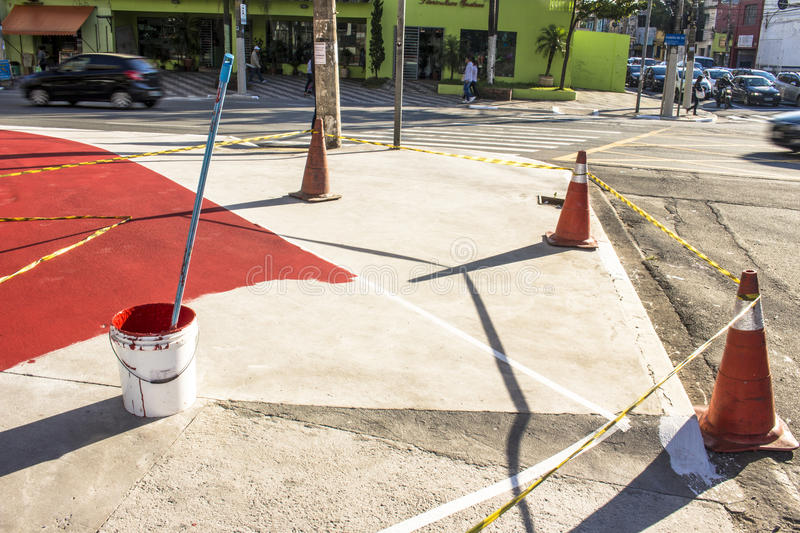 Bike lane. Sao Paulo, Brazil, June 15, 2016. Workers of the road marking the city, painted in red the central site of the Cruzeiro do Sul Avenue, which will be a royalty free stock images