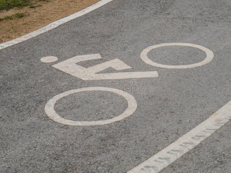 Bike lane sign with car wheel track stock photos