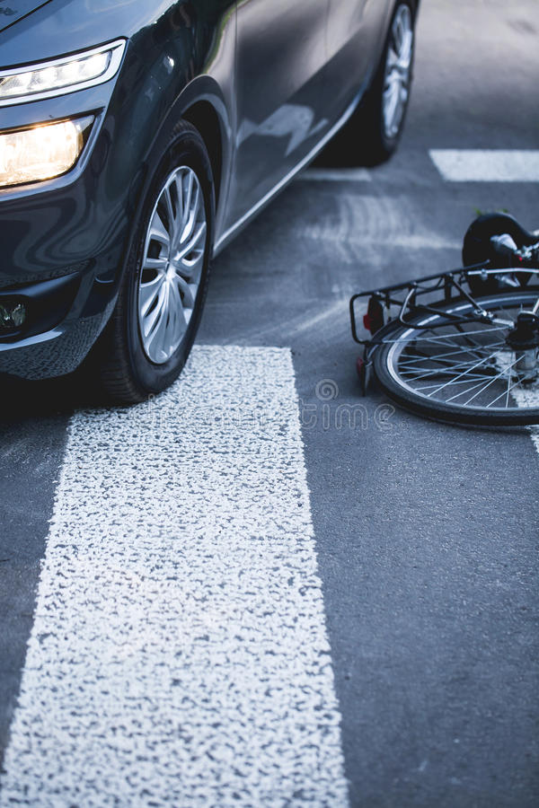 Bike lying next to a car on the pedestrian crossing stock images