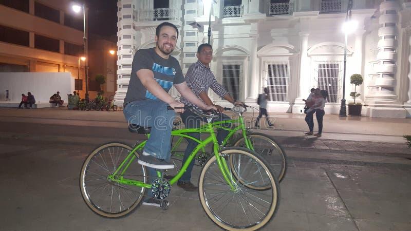 Bike a menina do tempo? com capacete de ciclagem e o outro passeio do protetor? um triciclo? imagem de stock royalty free