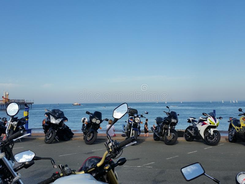 Bike Night Paignton Sea Front Motorbikes. Bike night at Paignton in Devon, UK with motorbikes parked along the sea front. There are sailing boats in the distance royalty free stock photo
