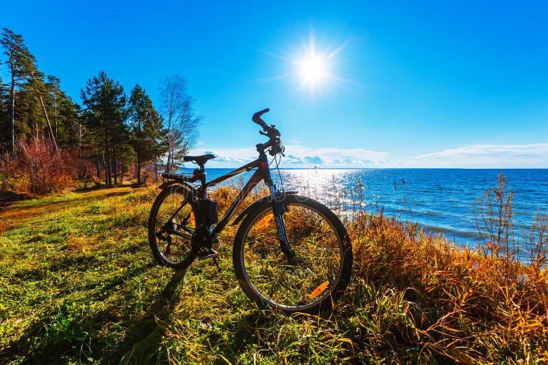 Bike no backlighting na costa do rio imagens de stock