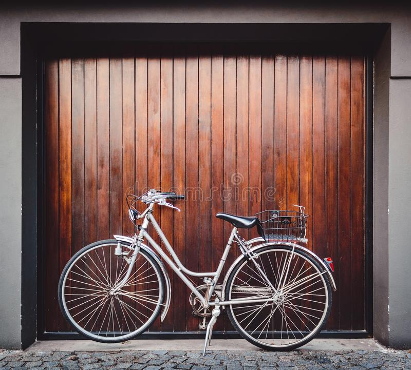 Bike parked in front of a garage door. Silver vintage bike parked inf front of a wood garage door royalty free stock image