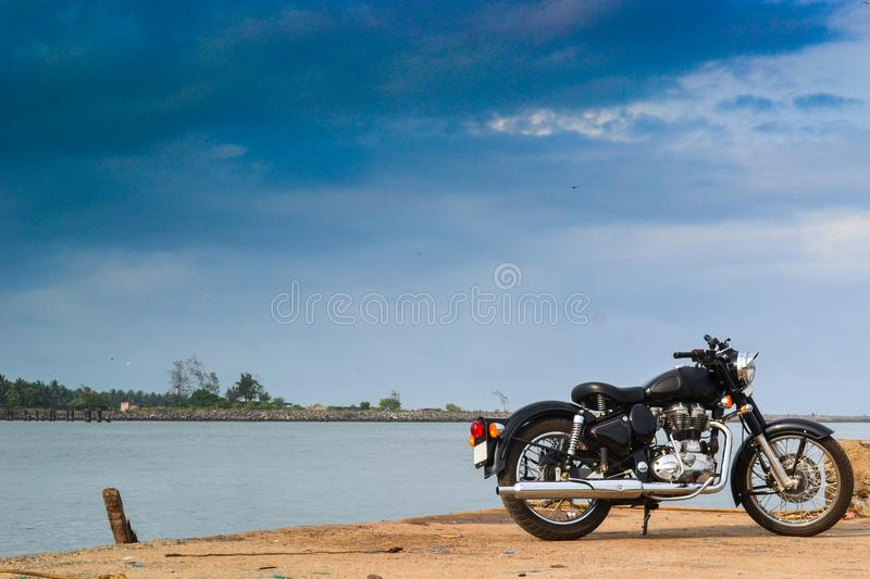 Bike parked near sea shore. Beautiful view of royal enfield parked near sea royalty free stock images