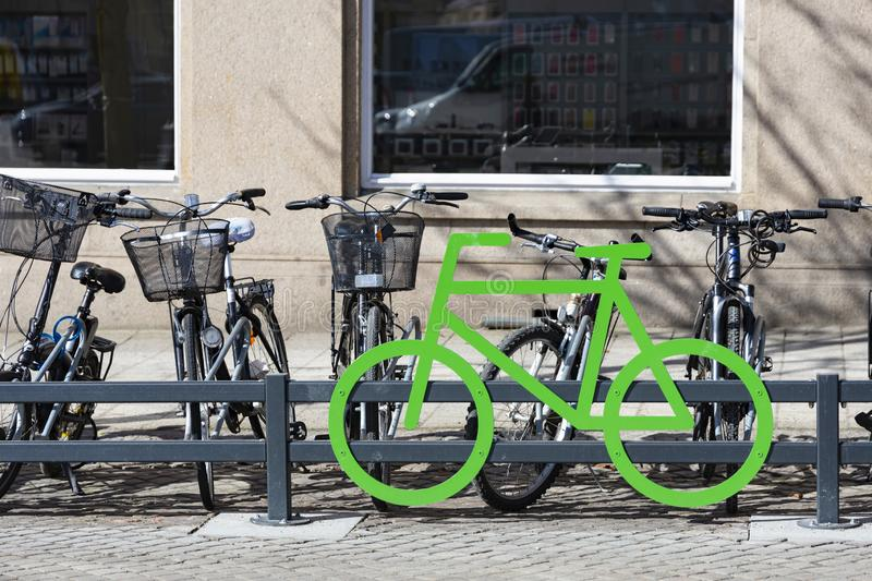 Bike parking in the center of the city. Green bike symbol, city bikes parked in a row near grey building. Bike parking in the centre of the city. Green bike royalty free stock photography