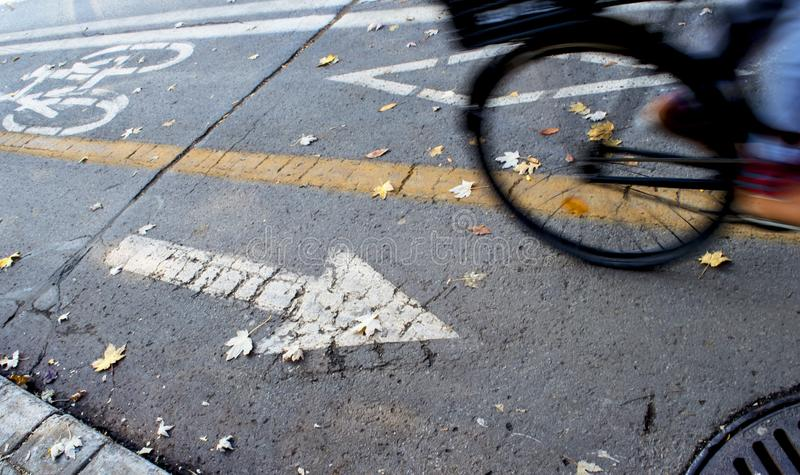 Bike path in city with bicycle wheel in motion royalty free stock photo