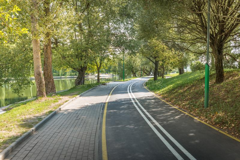 Bike path in the park with green trees. Beautiful summer landscape royalty free stock photography