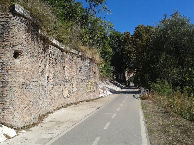 Bike a pista a Roma com uma parede antiga da pedra com alguns grafittis e vegetação ao redor, Itália imagens de stock