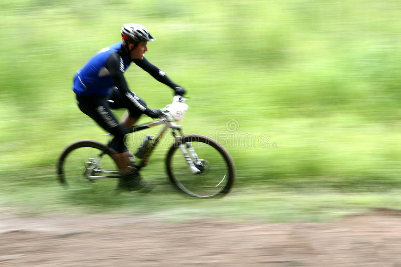Bike race. Mountain bike race in a forest in denmark, Shot with low shutter speed to achieve motion blur royalty free stock image