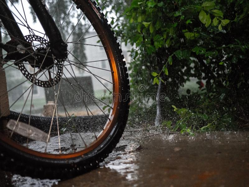 Bike in Rain. Wet bike left out in the rain for a high action shot with the rain drops splashing against the ground royalty free stock photos