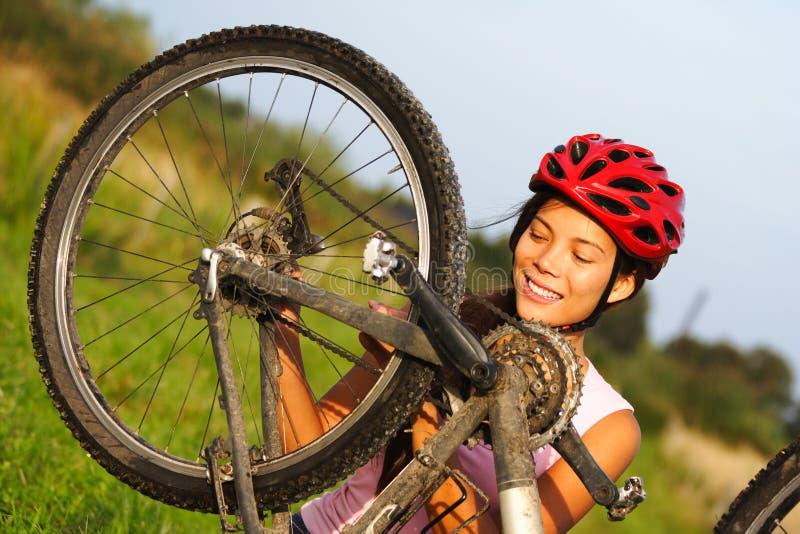 Bike repair. Woman repairing mountain bike. Beautiful smiling woman stock image