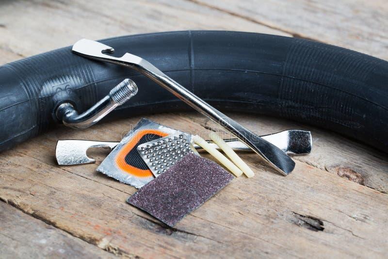 Bike repair kit. Closeup of bike tire repair kit on wooden table stock images