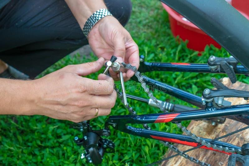Bike repair. Young man repairing bike in the forest stock images