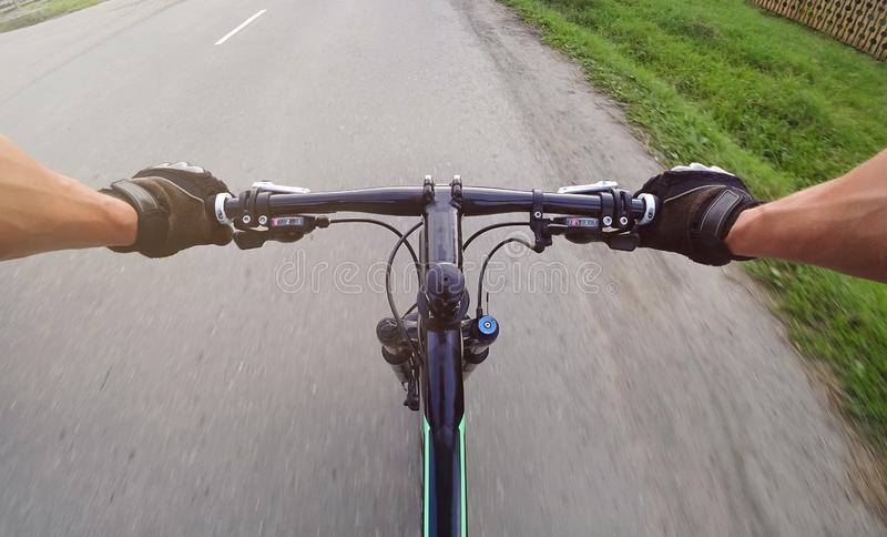 Bike ride. Driving a mountain bike in the first person. Gloved hand stock image