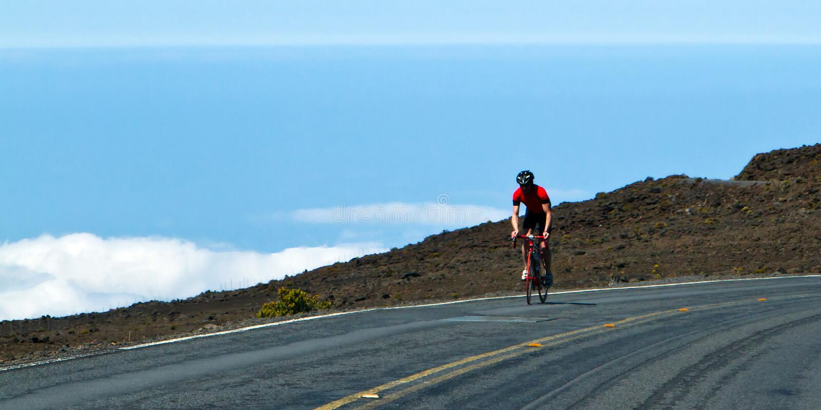 Bike rider above the clouds stock photography