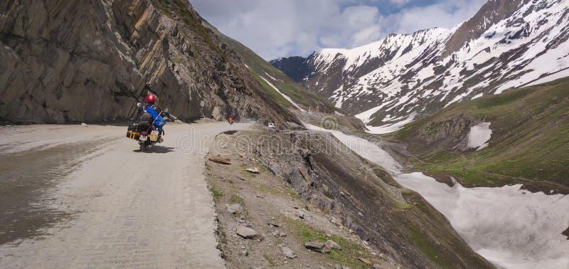 A bike rider crossing the zojila pass at an elevation of 11,000 ft. at Jammu and Kashmir. Way towards Drass and Kargil royalty free stock photos