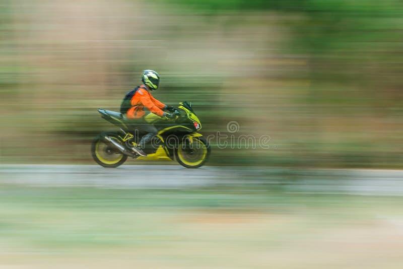 Bike rider in motion blur panning. Bike rider in motion blur panning photo of unidentified people riding motorcycle royalty free stock photo