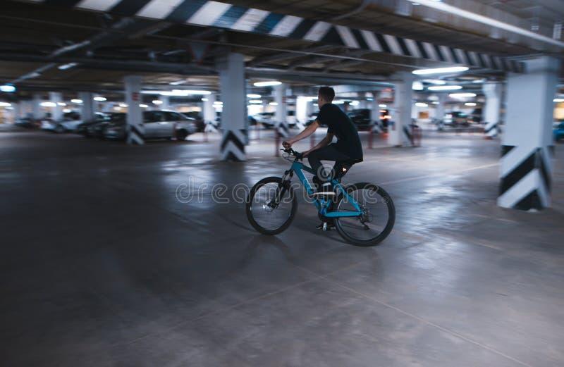 rider rides on an underground parking lot. A cyclist rides in an underground parking lot stock image