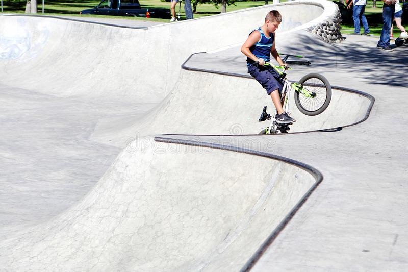 Bike rider in a Skatepark. Idaho Falls, Idaho, USA A 12 year old boy rides a bicycle in the bowl of a modern concrete skatepark stock photos