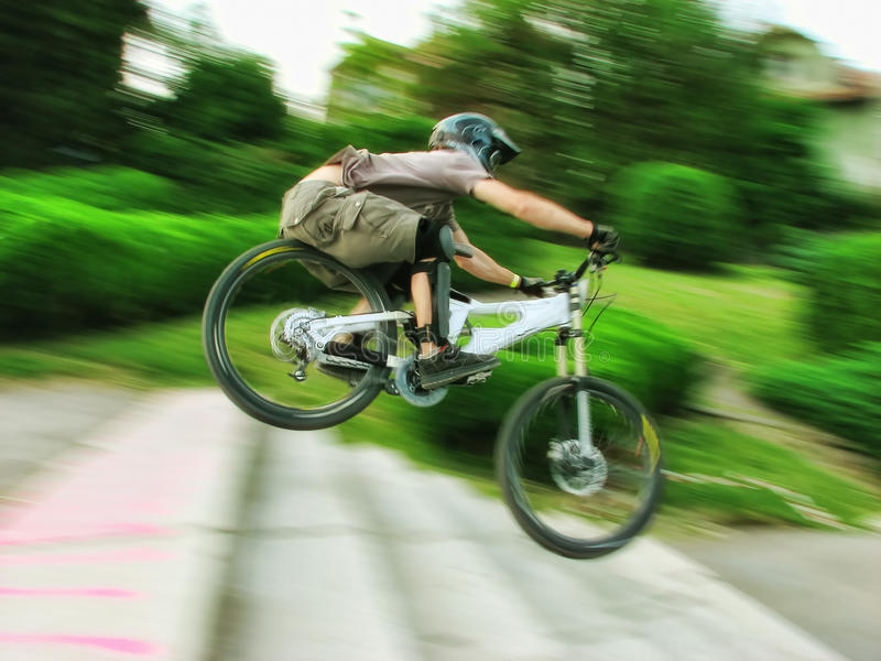 Bike rider at urban downhill competition. Unknown professional biker jumping over stairs with high speed at urban downhill competition on May 31, 2008 at Cluj royalty free stock photos