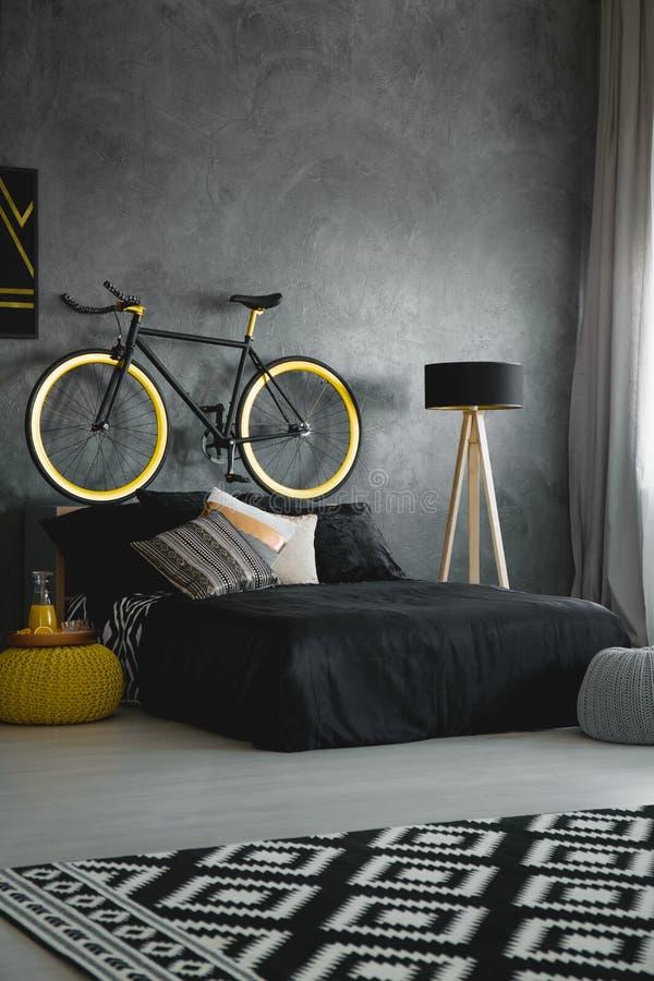 Bike sopra il letto nero contro il muro di cemento in camera da letto moderna int immagine stock