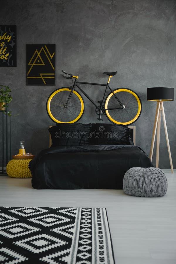 Bike sopra il letto nero nell'interno grigio moderno della camera da letto con il picchiettio fotografia stock