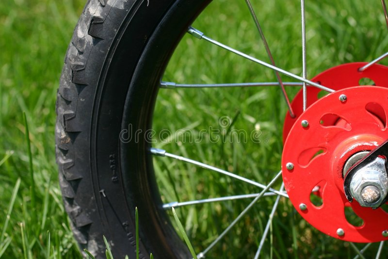 Bike Tire. Child's red bike tire in the grass royalty free stock images