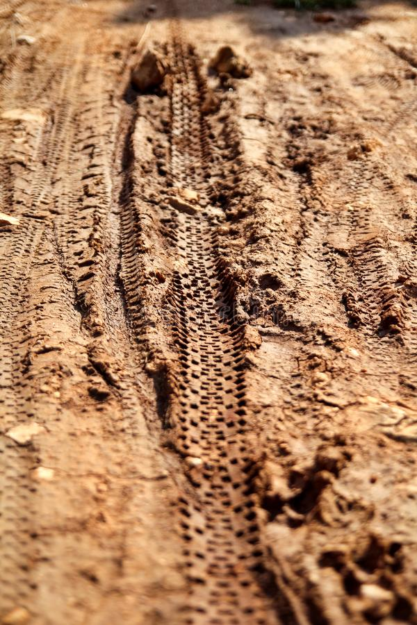 Bike tire tracks on muddy trail royalty. Tire tracks on wet muddy road, abstract background, texture material. Tyre track on dirt sand or mud, retro tone royalty free stock photos