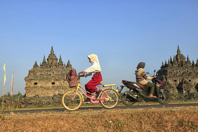 Bike to School. Students are going to school by bicycle across the Plaosan Temple area, Yogyakarta, Indonesia, on August 27, 2018 stock images