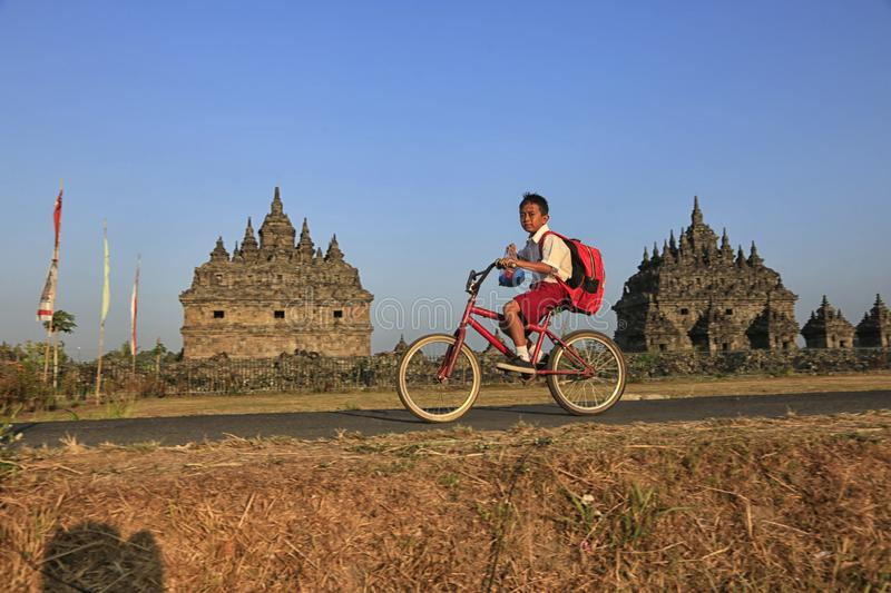 Bike to School. Students are going to school by bicycle across the Plaosan Temple area, Yogyakarta, Indonesia, on August 27, 2018 stock photography