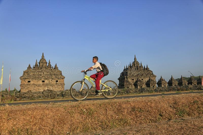 Bike to School. Students are going to school by bicycle across the Plaosan Temple area, Yogyakarta, Indonesia, on August 27, 2018 royalty free stock images