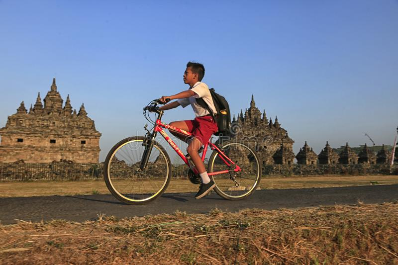 Bike to School. Students are going to school by bicycle across the Plaosan Temple area, Yogyakarta, Indonesia, on August 27, 2018 royalty free stock photo