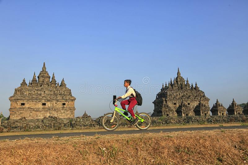 Bike to School. Students are going to school by bicycle across the Plaosan Temple area, Yogyakarta, Indonesia, on August 27, 2018 stock photo