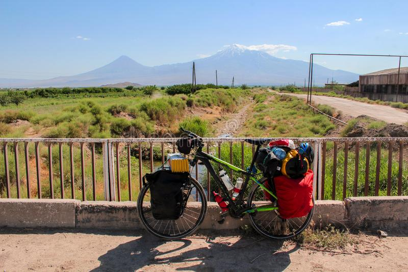 Bike touring in Armenia with mount Ararat as background and a stream royalty free stock images