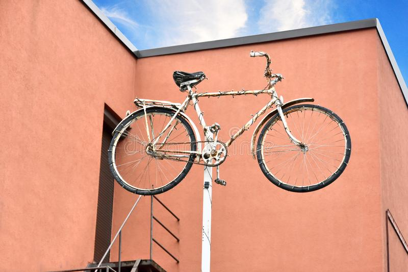 Bike up on a mast, eye catcher for a repair service. Bike mounted high up on a mast, eye catcher for a repair service or a bike rental stock images