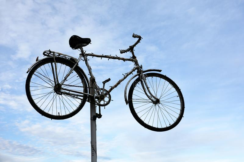 Bike up on a mast, eye catcher for a repair service. Bike mounted high up on a mast, eye catcher for a repair service or a bike rental stock photo