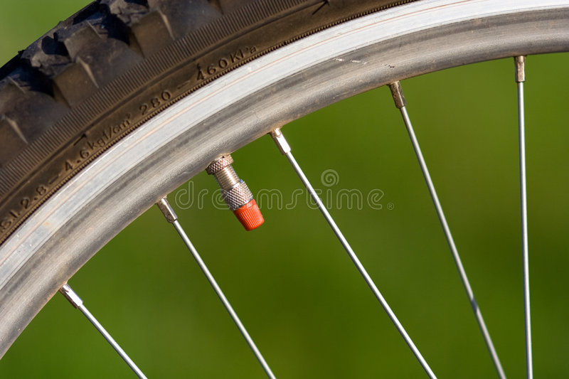 Bike wheel. Part of a sport bike wheel on green backgound royalty free stock images