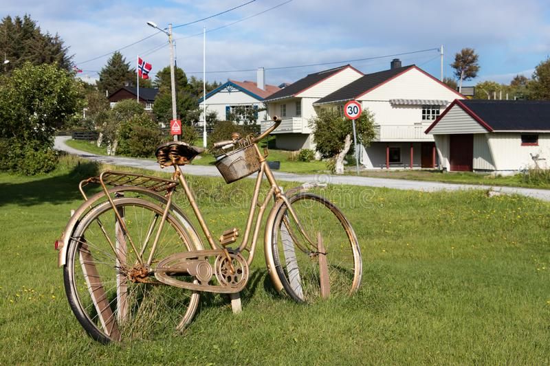 A bike and wooden local houses at the village of Dyrnes at Smola island, Norway. Dyrnes, Smola, Norway - August 30th, 2018: A bike and wooden local houses at the royalty free stock photo