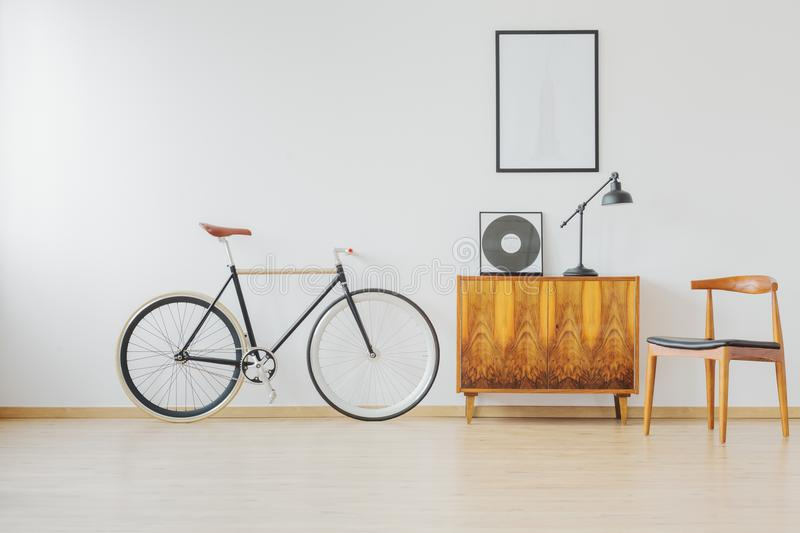 Bike and wooden retro furniture. Modern and stylish vintage apartment for hipster student with bike and wooden retro furniture royalty free stock photography