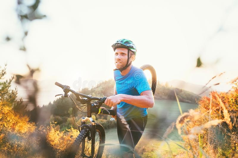 Cyclo-cross competition member Man mountain biker carrying his bike up on hill top royalty free stock photos