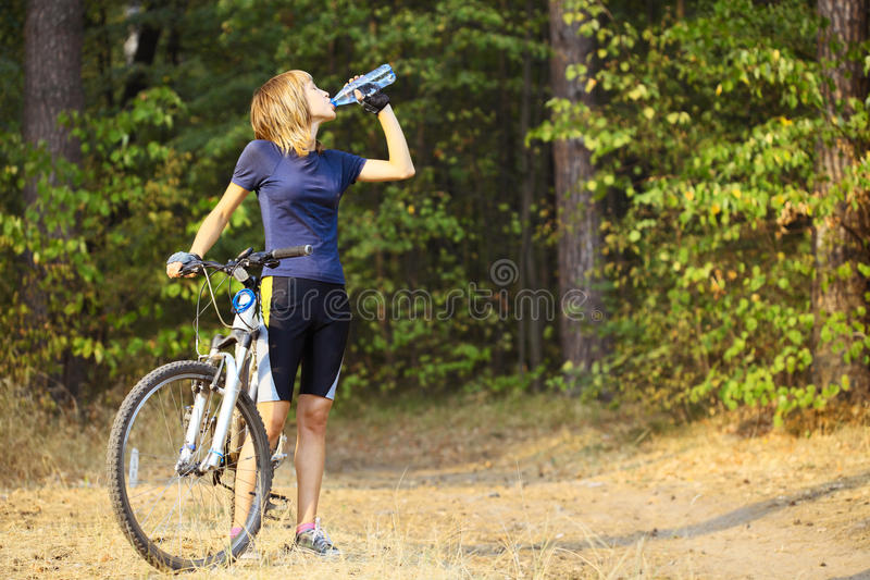 Biker. Young woman with bike drinking wter from bottle royalty free stock photo