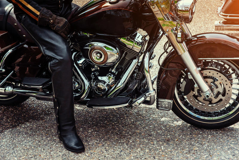 Biker in black boots sitting on a motorcycle. On the side of the road. Kind of sport stock photos