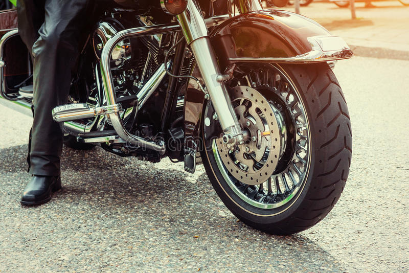 Biker in black boots sitting on a motorcycle. On the side of the road. Kind of sport stock images