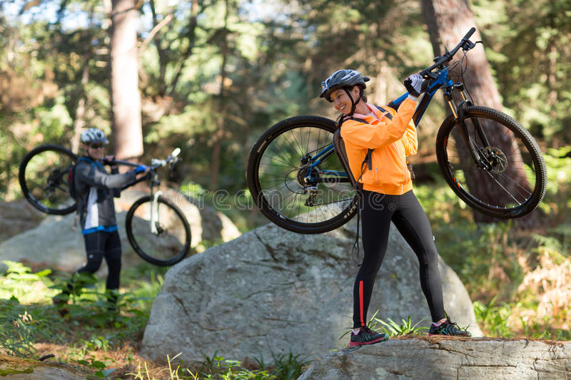 Biker couple holding their mountain bike and walking in forest. Biker couple holding their mountain bike and walking in countryside forest stock photography