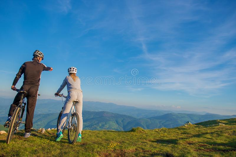 Biker couple with mountain bike pointing in distance at countryside royalty free stock photography