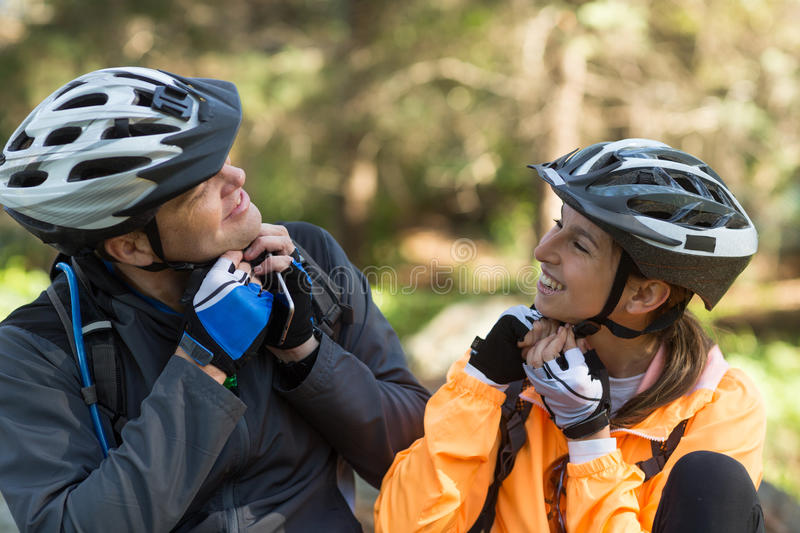Biker couple wearing bicycle helmet in forest. At countryside stock photography
