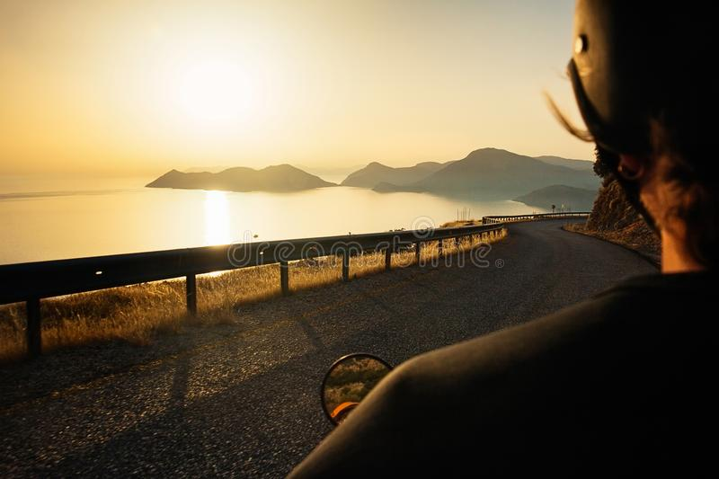 Biker driving along the mountain road at sunset over the sea, bl royalty free stock images
