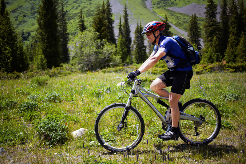 Biker on footpath in mountains royalty free stock photo